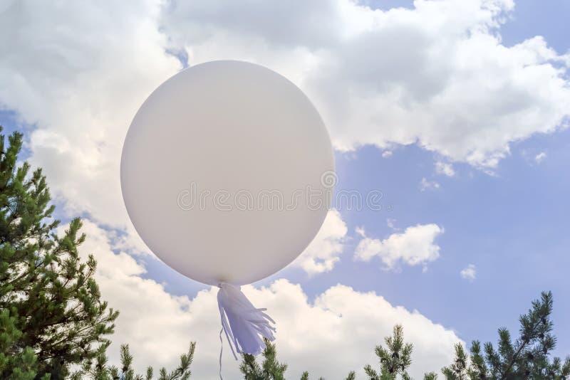 Globo ligero contra el cielo con las nubes y los árboles imágenes de archivo libres de regalías