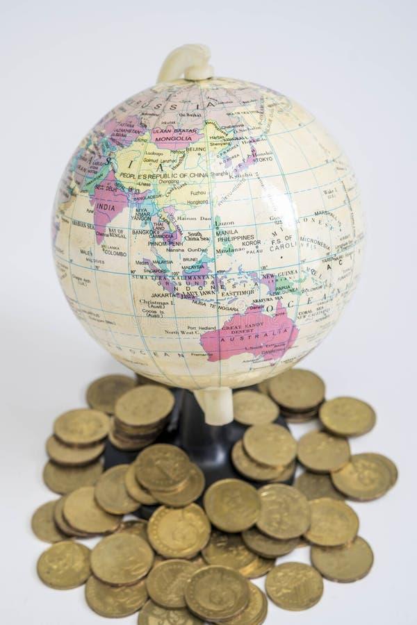 Globo miniatura con las monedas fotos de archivo