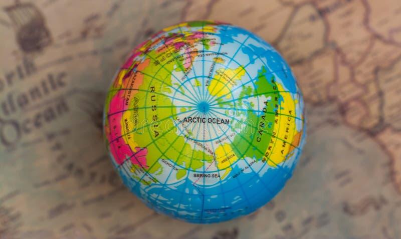 Globo multicolor contra la perspectiva del mapa del mundo, visión superior, imagen de archivo