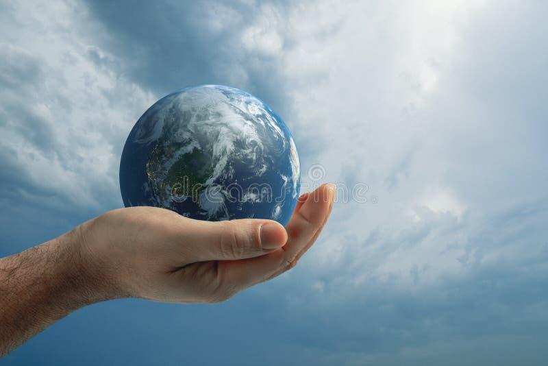 Globo na mão humana de encontro ao céu azul Conceito da proteção ambiental imagem de stock royalty free