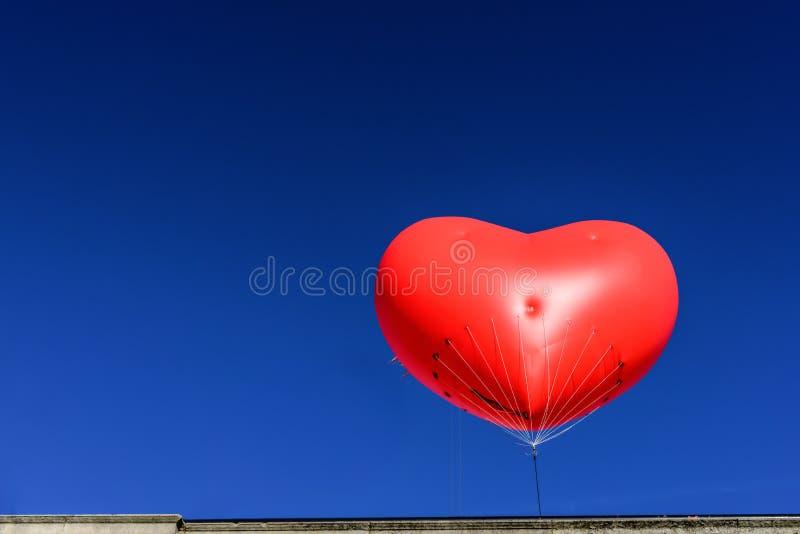 Globo rojo grande del corazón con el fondo claro de cielo azul fotografía de archivo