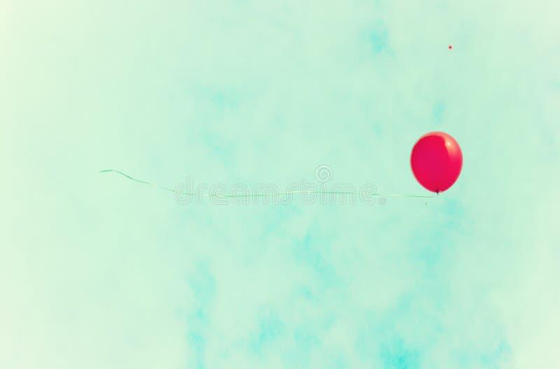 Globo rojo sobre un cielo retro foto de archivo