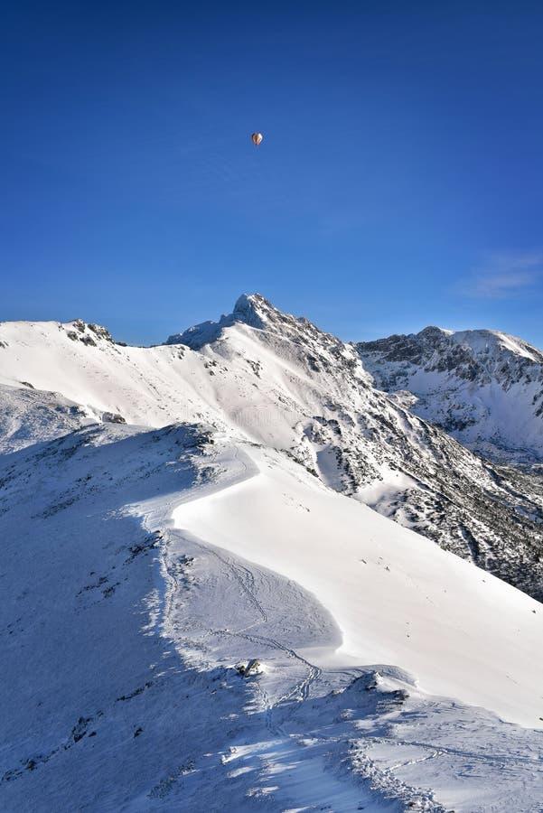 Globo sobre el pico nevoso de Swinica Montaña de Tatra foto de archivo