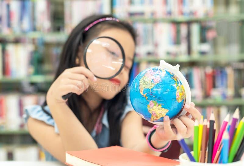 Globo sonriente de la tierra el estudiar y de la educación del niño del asiático del estudiante en la biblioteca, foco selecto fotos de archivo