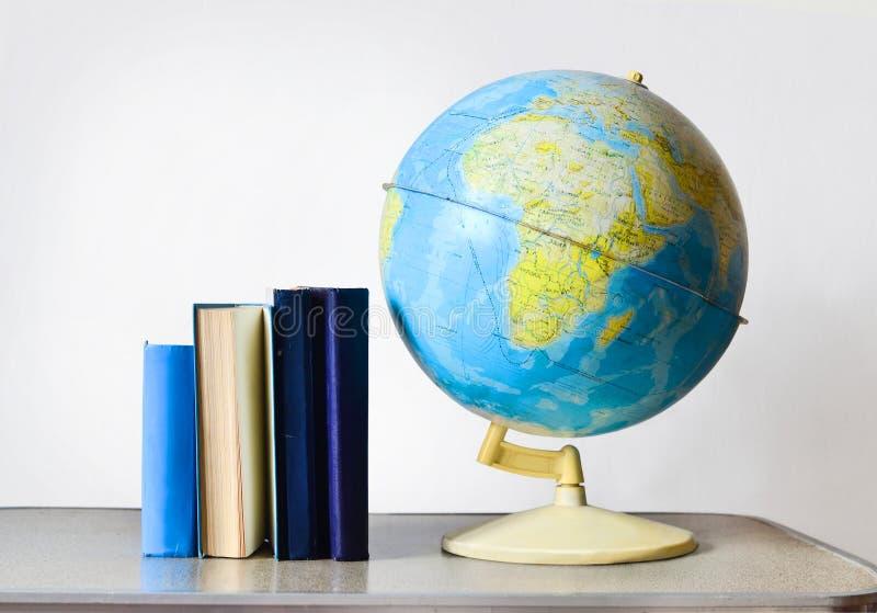 Globo y libros de la escuela del vintage en la tabla imagen de archivo