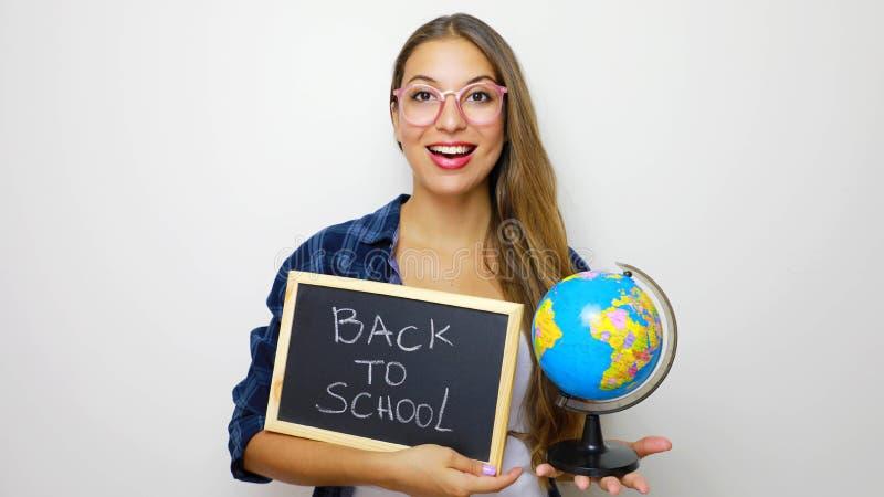 Globo y pizarra jovenes hermosos de la tenencia del estudiante con escrito de nuevo a escuela fotografía de archivo libre de regalías