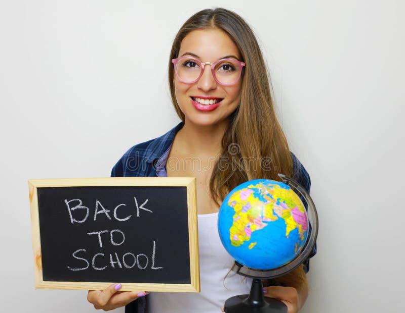 Globo y pizarra jovenes hermosos de la tenencia del estudiante con escrito de nuevo a escuela foto de archivo