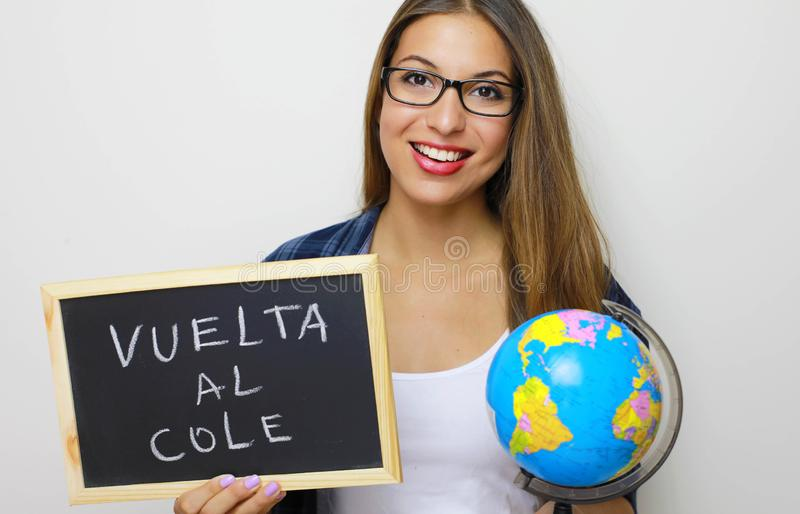 Globo y pizarra jovenes latinos de la tenencia de la maestra con el español escrito fotografía de archivo