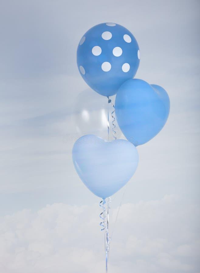 Globos azules en forma del corazón y lunar sobre fondo del cielo azul con efecto retro del filtro foto de archivo