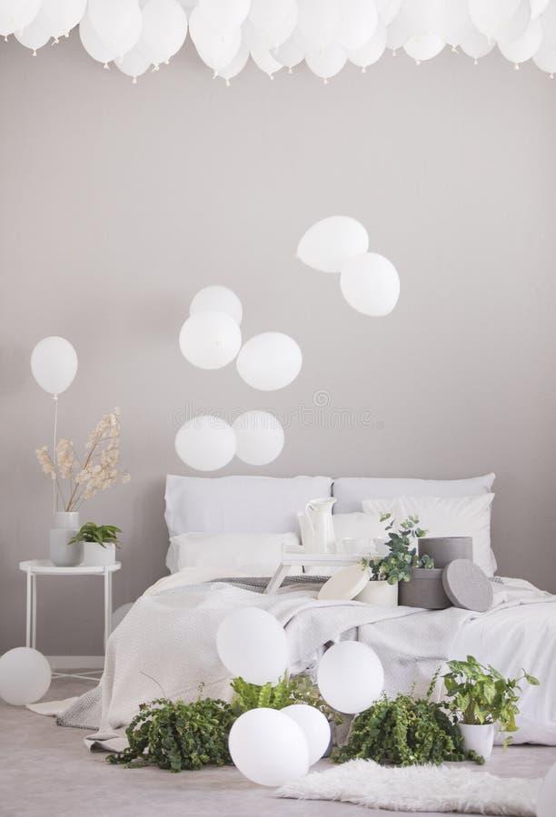 Globos blancos bajo techo del dormitorio escandinavo gris con la cama matrimonial y de plantas verdes en los potes, foto real con imágenes de archivo libres de regalías