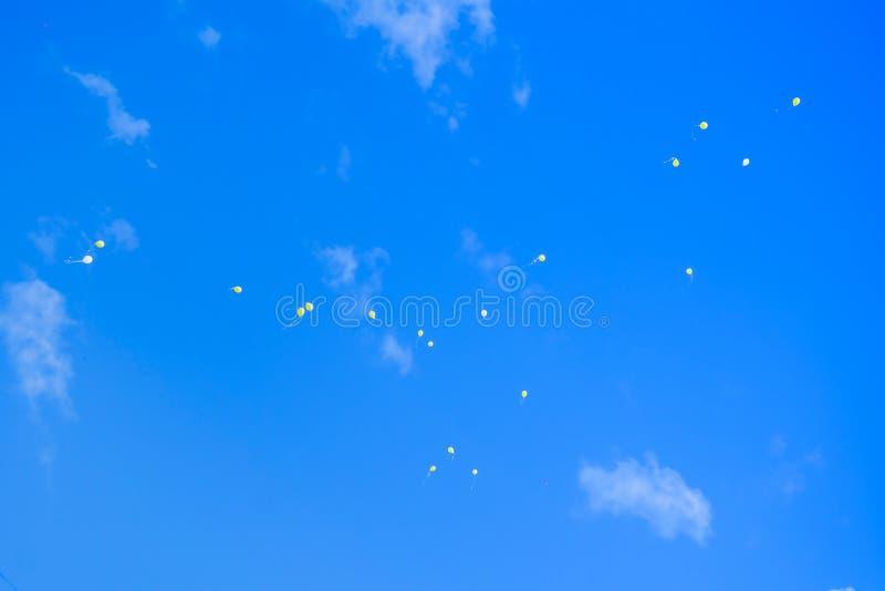Globos coloridos del helio en vuelo contra el cielo azul, saludos del cumpleaños foto de archivo