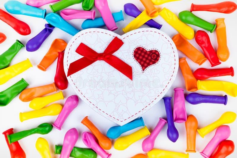Globos coloridos en caja de regalo del corazón Fondo blanco fotos de archivo libres de regalías