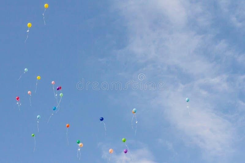 Globos coloridos en fondo del cielo nublado azul los globos lanzaron en el cielo foto de archivo libre de regalías