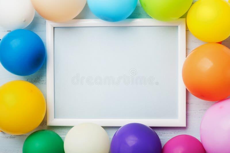 Globos coloridos y marco blanco en la opinión de sobremesa de madera azul Maqueta para el cumpleaños o el partido de planificació fotografía de archivo