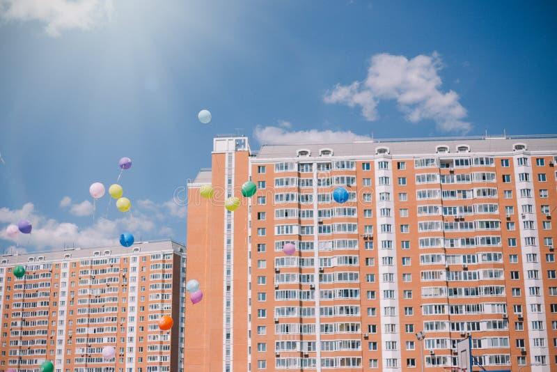Globos contra el cielo azul, las nubes y los edificios residenciales Última llamada y graduación en la escuela fotos de archivo