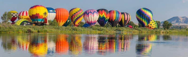 Globos del aire caliente a lo largo del panorama del río imagenes de archivo