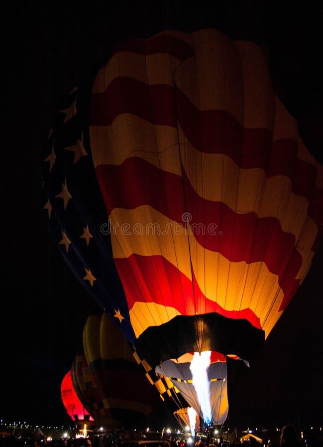 Globos del aire caliente que brillan intensamente en la noche fotos de archivo