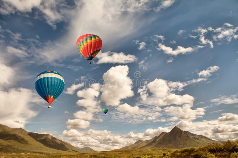 Globos del aire caliente sobre las montañas foto de archivo
