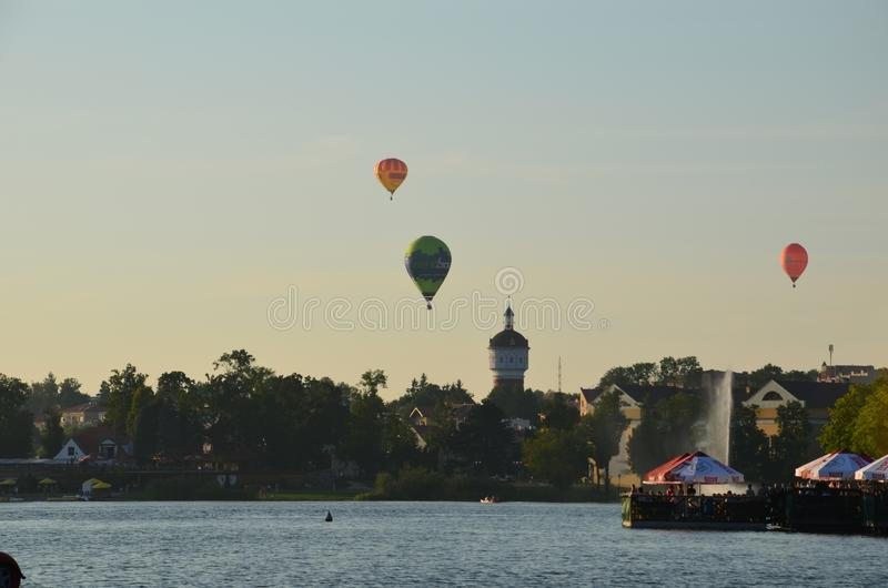 Globos del aire caliente sobre un lago en la opinión de Polonia durante puesta del sol imagen de archivo libre de regalías