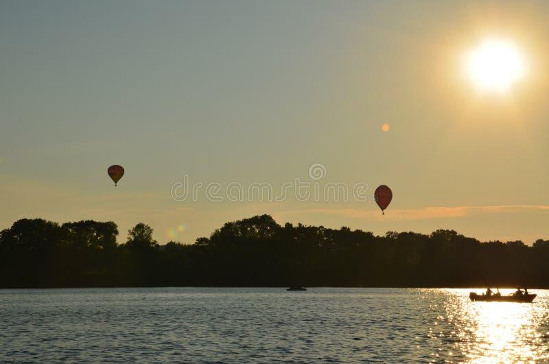Globos del aire caliente sobre un lago en la opini?n de Polonia durante puesta del sol fotografía de archivo