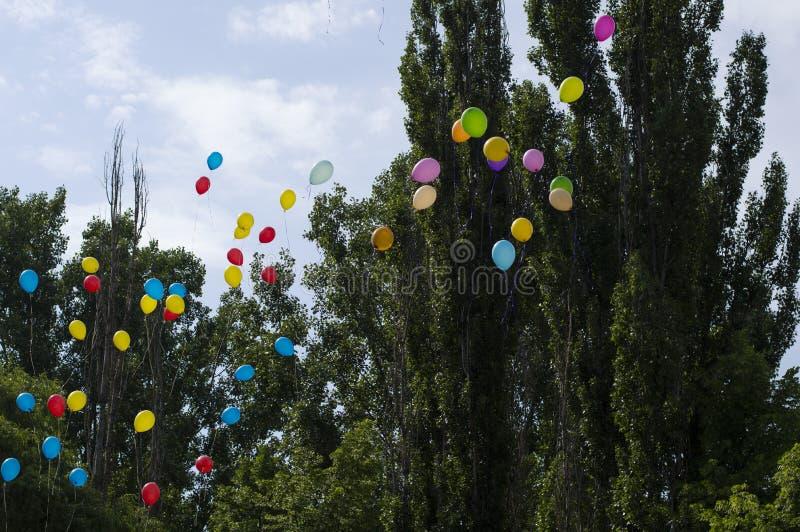Globos en el cielo contra árboles y el cielo, la escuela de la última llamada imagenes de archivo