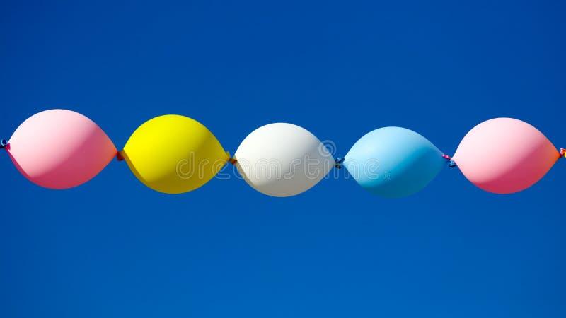 Globos festivos multicolores contra el cielo azul fotografía de archivo