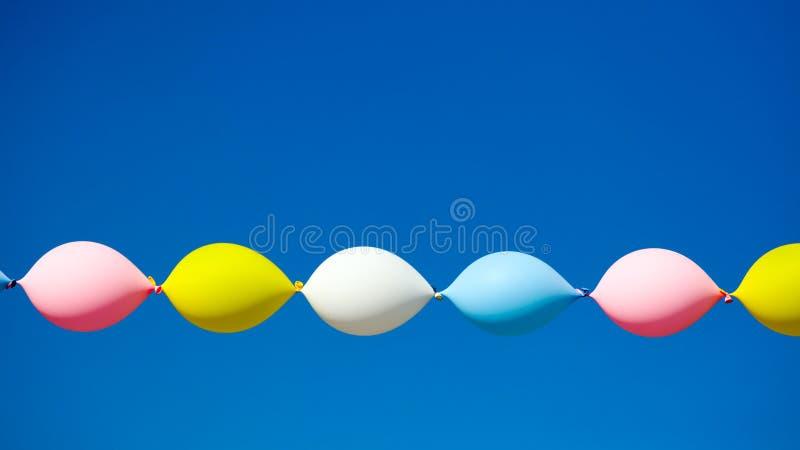 Globos festivos multicolores contra el cielo azul foto de archivo