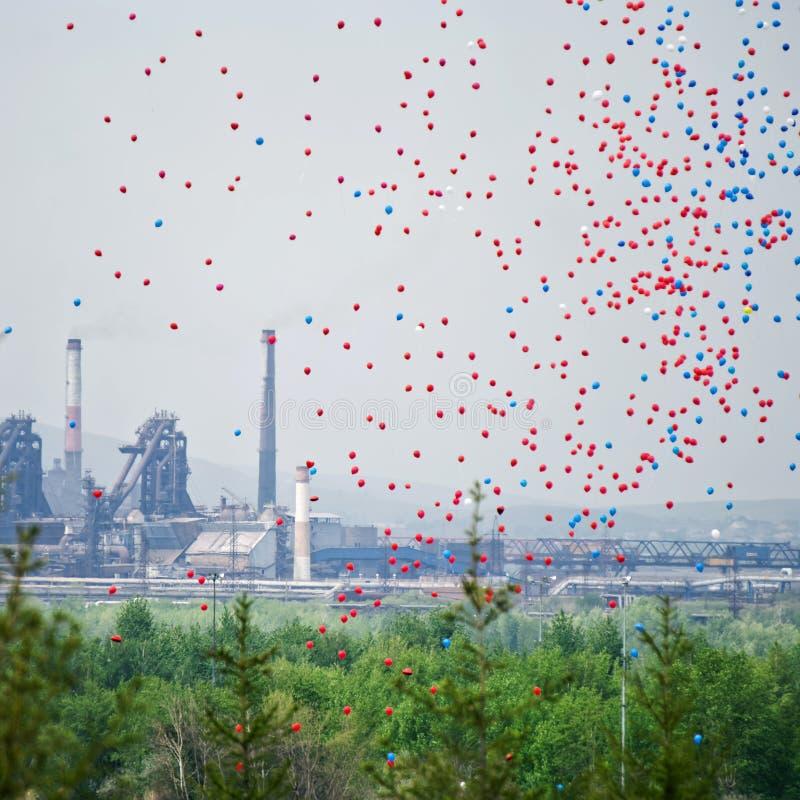 Globos multicolores en el cielo contra la perspectiva de los tubos de una planta metalúrgica grande Contrastes de la naturaleza,  imagenes de archivo