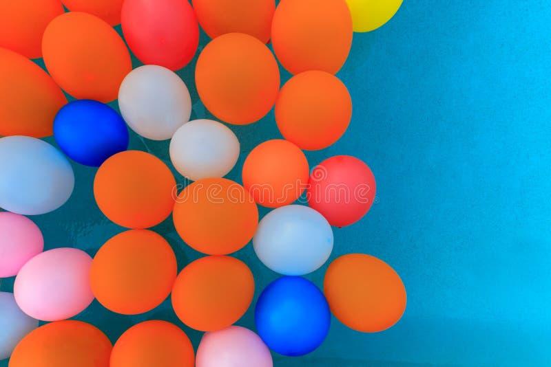 Globos multicolores que flotan en piscina fotografía de archivo