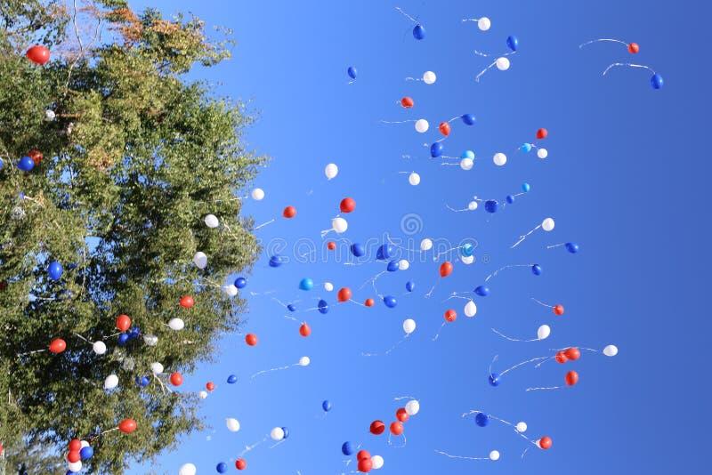 Globos multicolores que se lanzan en vuelo libre fotografía de archivo