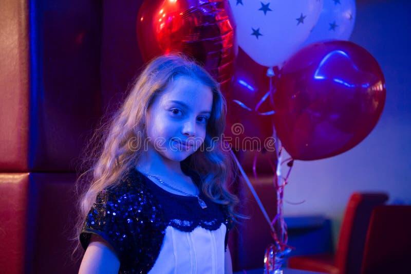Globos sonrientes lindos del manojo del control del niño de la muchacha encendidos con la luz azul La muchacha con los globos cel foto de archivo libre de regalías