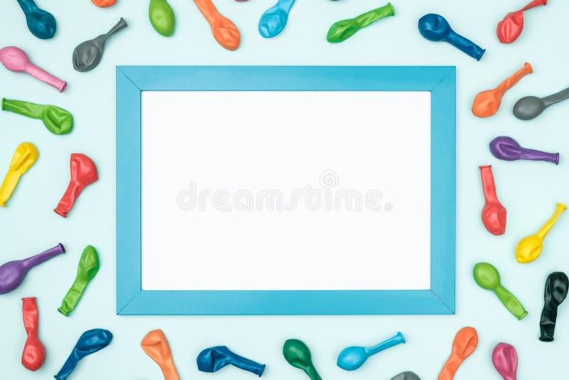 Globos y marco coloridos en la opinión superior del fondo colorido Maqueta del cumpleaños o del partido fotografía de archivo libre de regalías