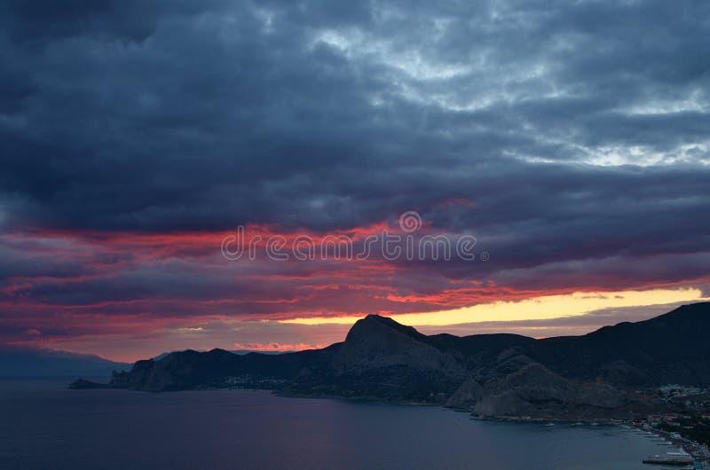 Gloed in bewolkte hemel na zonsondergang op schilderachtige overzeese kust stock fotografie