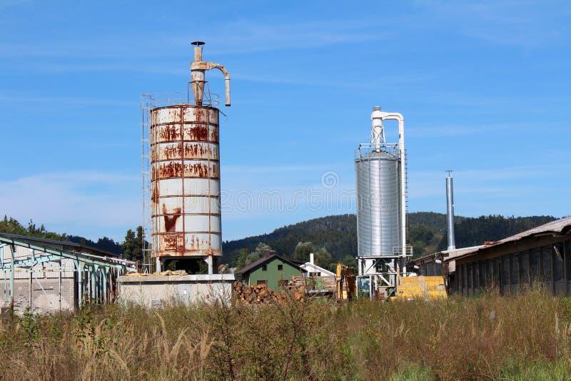 Gloednieuw glanzend metaal en oude geroeste lange die opslagsilo's met verlaten fabrieksgebouwen en bouwmateriaal wordt omringd m stock foto