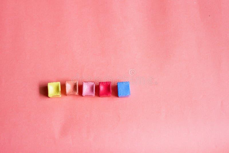 Gloednieuwe kleurrijke waterverfpannen, geel, oranje, roze, rood en blauw, voor waterverfpallet op roze-oranje achtergrond met ex royalty-vrije stock foto's