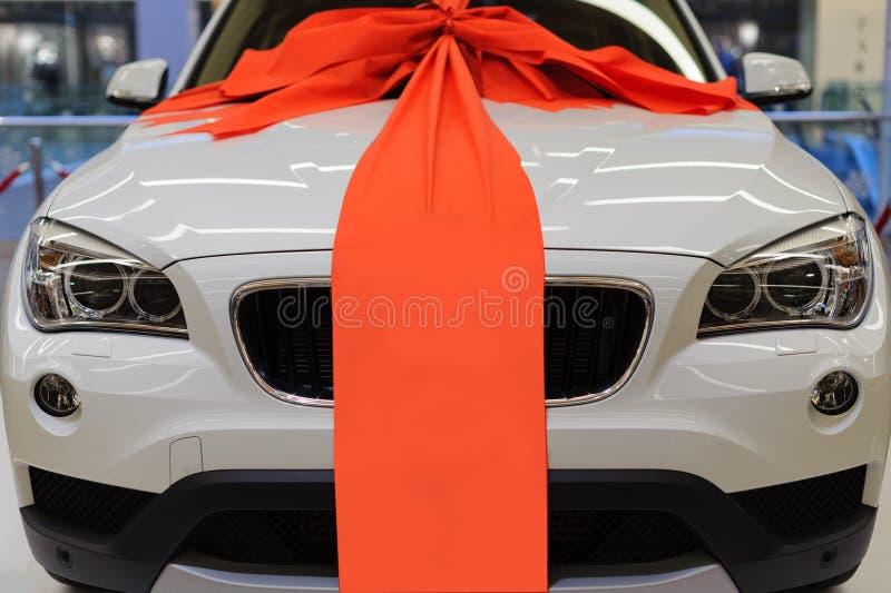 Gloednieuwe witte huidige auto met grote rode lintdecoratie stock foto's
