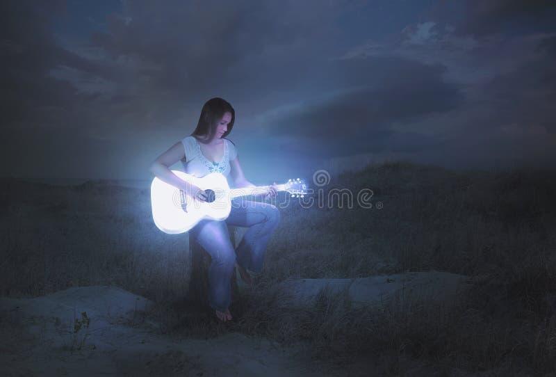 Gloeiende gitaar bij nacht stock afbeeldingen