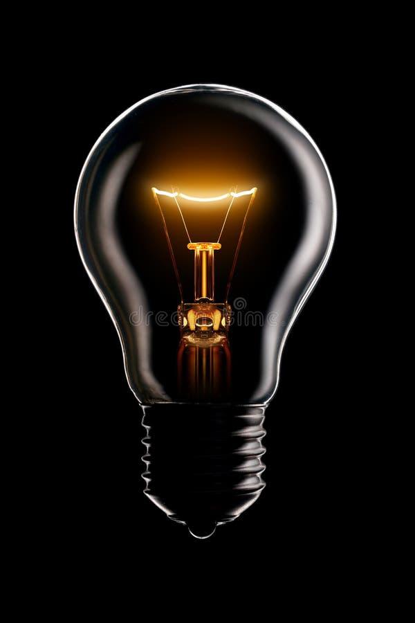 Gloeiende lamp op zwarte stock afbeelding