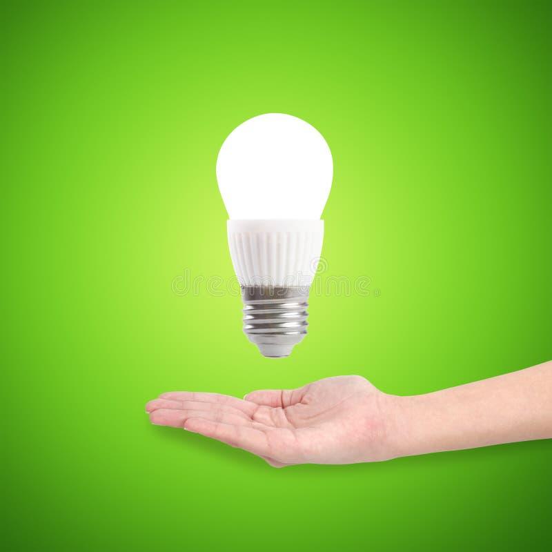 Gloeiende LEIDENE energie - besparingsbol in een hand royalty-vrije stock afbeelding