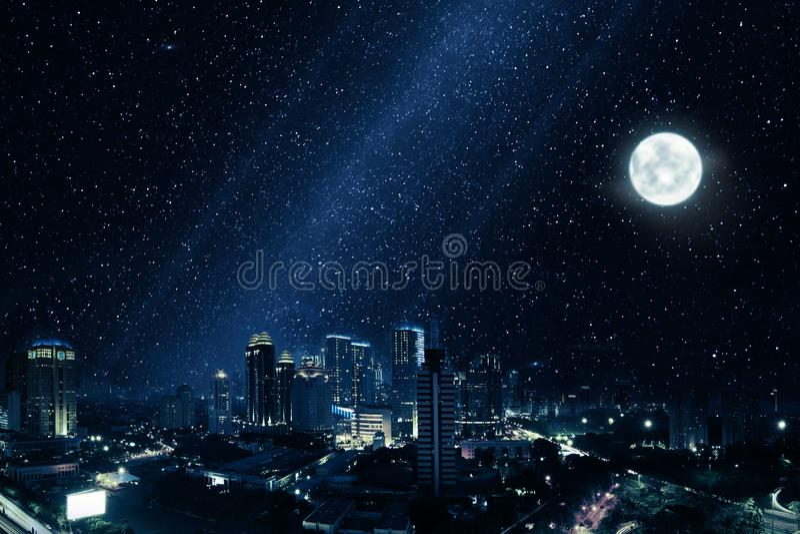 Gloeiende stad met heldere maan en vele sterren in hemel royalty-vrije stock afbeelding