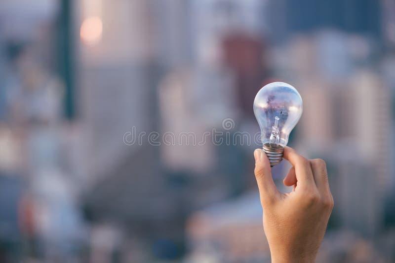Gloeilamp boven Zonsondergang stedelijke huizen bol transparante lamp in man alternatieve zonne-energie in stedelijk, stad, het l stock afbeelding