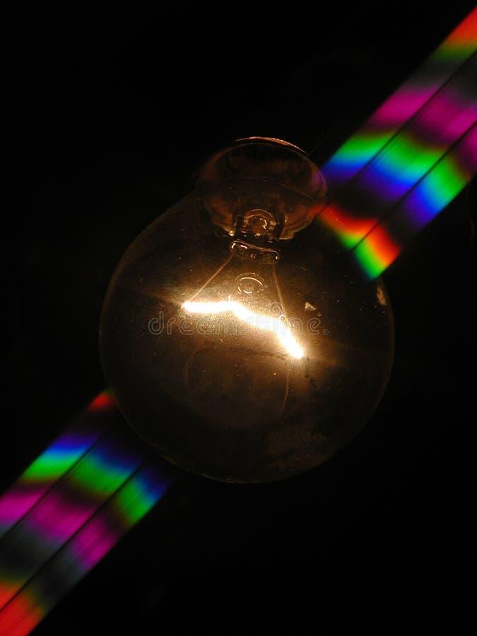Gloeilamp en regenboog stock fotografie