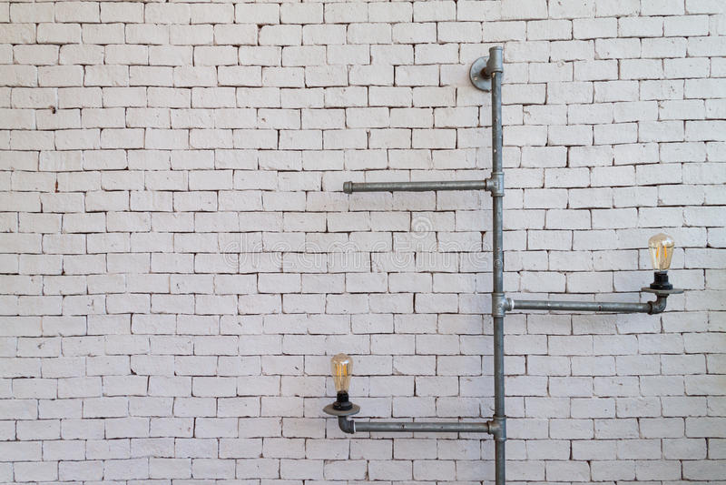 Gloeilamp met metaalpijp over baksteenachtergrond stock foto's