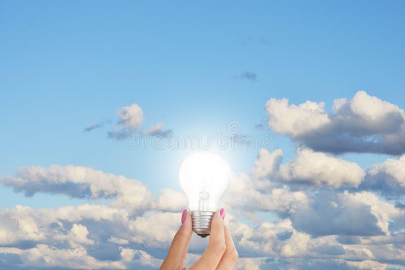 Gloeilamp in vrouwenhand tegen blauwe hemel die creativiteitconcept voorstellen stock foto