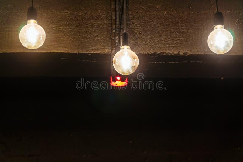 Gloeilampen tegen het donkere plafond stock afbeeldingen