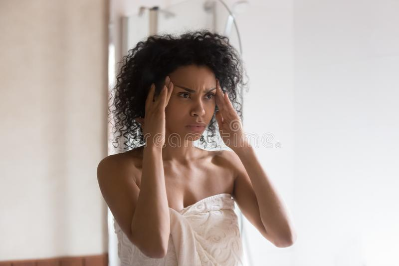 Anxious african American woman worried about face wrinkles. Gloomy african American millennial woman in shower towel look in mirror worry about face wrinkles stock images