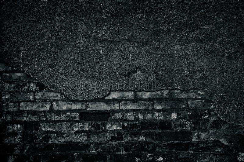 Gloomy black and white background of old shabby dark brick wall stock photo