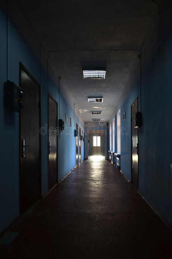 The gloomy corridor of a neglected public building. Public space in a poor residential high-rise buildin. G royalty free stock image