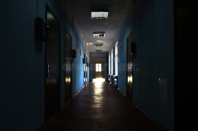 The gloomy corridor of a neglected public building. Public space in a poor residential high-rise buildin. G stock image
