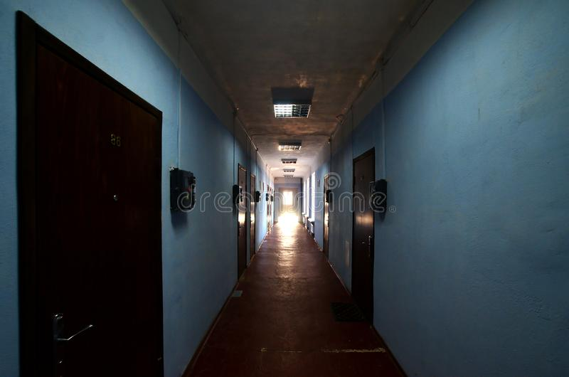 The gloomy corridor of a neglected public building. Public space in a poor residential high-rise buildin. G royalty free stock photos